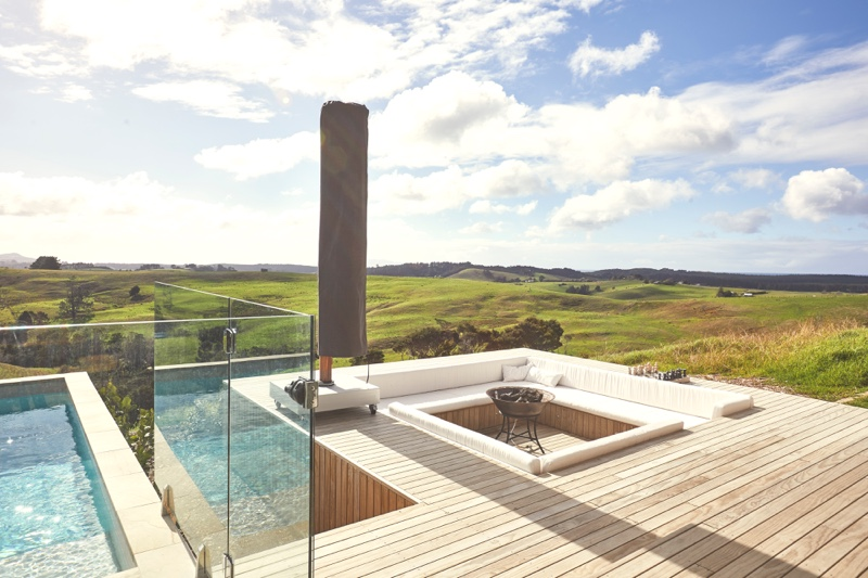A photo of a modern deck with pool looking out over Te Arai Estate